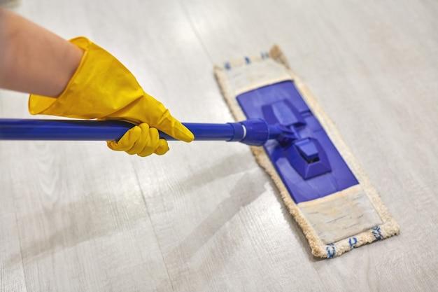 Młoda kobieta w ochronnych żółtych gumowych rękawiczkach za pomocą płaskiego mokrego mopa podczas czyszczenia podłogi w domu.