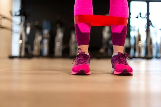 Młoda kobieta w odzież sportowa ćwiczenia sportowe z dopasowanie gumką na nogi w siłowni. styl życia fitness i wellness