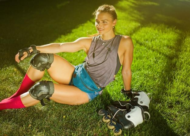 Młoda kobieta w odzieży ochronnej i rolkach odpoczywa w parku na trawie.