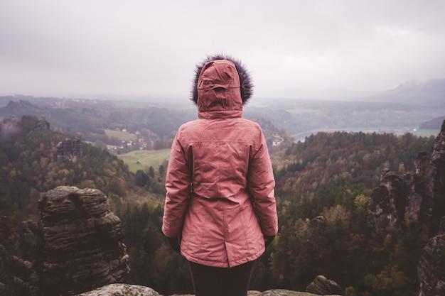 Młoda kobieta w odzieży outdoorowej stojącej samotnie na szczycie góry z dzikim lasem w dolinie
