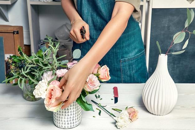 Młoda kobieta w odzieży roboczej pracuje w kwiaciarni. przycięty obraz kwiaciarni układania bukietu. obraz, koncepcja dostawy kwiatów, sprzedaż i florystyka. skopiuj miejsce na projekt