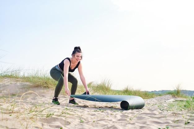 Młoda kobieta w odzieży sportowej przygotowuje matę do ćwiczeń