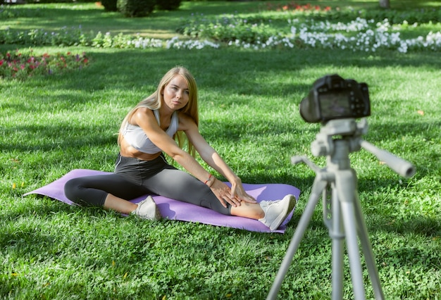 Młoda kobieta w odzieży sportowej siedzi na macie do jogi w parku i rozciąga się podczas kręcenia kamery na świeżym powietrzu. blog fitness