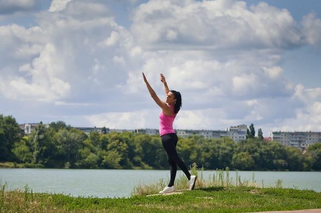 Młoda kobieta w odzieży sportowej uprawia sport na jeziorze w mieście