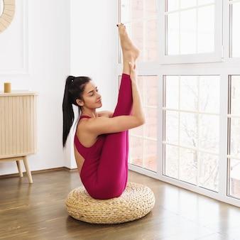 Młoda kobieta w odzieży sportowej uprawiająca jogę siedzi na podłodze, wykonując ćwiczenia urdhva mukha paschimottanasana w pokoju w pobliżu dużego okna