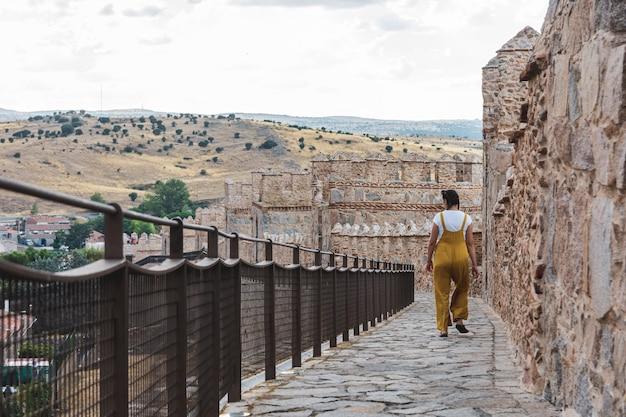 Młoda kobieta w ogrodniczkach spaceru wzdłuż średniowiecznych murów miasta avila, hiszpania.