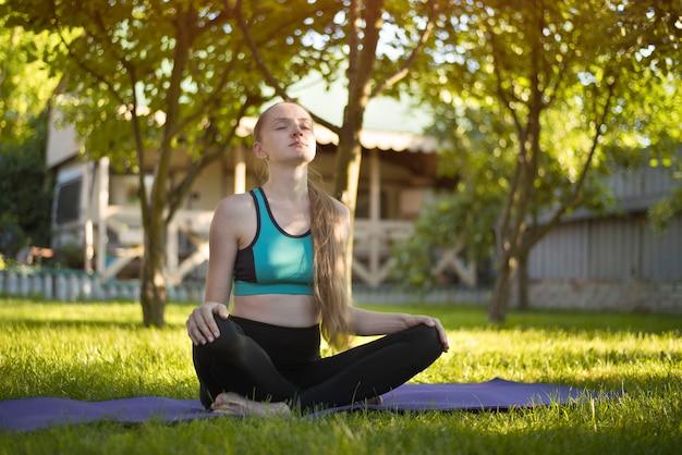 Młoda kobieta w ogrodzie siedzi na matę do jogi. letni poranek