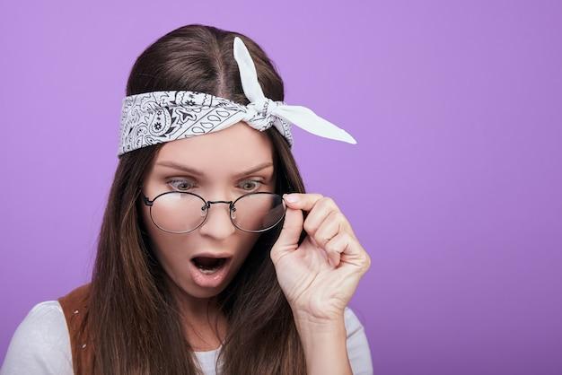 Młoda kobieta w okrągłych okularach patrzy z zaskoczeniem na dół.