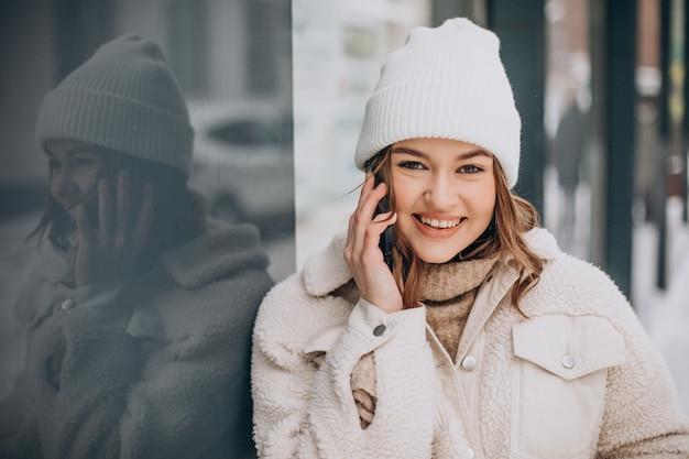 Młoda kobieta w okresie zimowym za pomocą telefonu poza ulicą