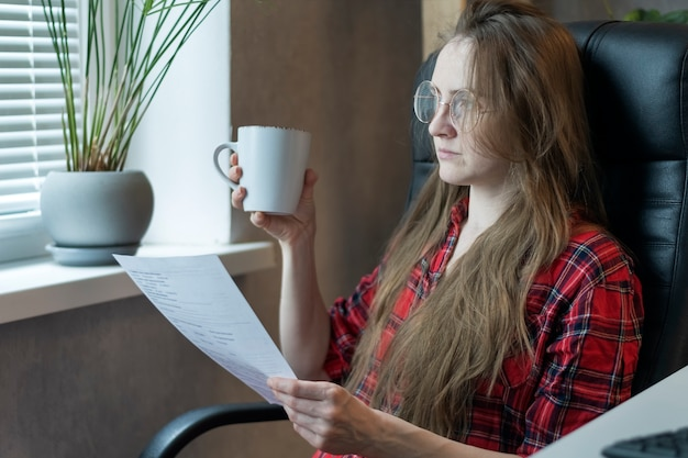 Młoda kobieta w okularach ćwiczy podczas przerwy na lunch. dokumenty i kubek herbaty w rękach.