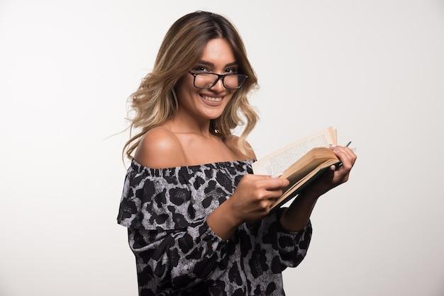 Młoda kobieta w okularach czyta książkę na białej ścianie.