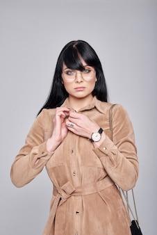 Młoda kobieta w okularach, elegancka brązowa sukienka. dziewczyna pozuje na szarej ścianie. fryzura. dziewczyna z czarną torebką. fotografia mody