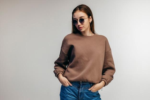 Młoda kobieta w okularach i pozowanie bluza z kapturem