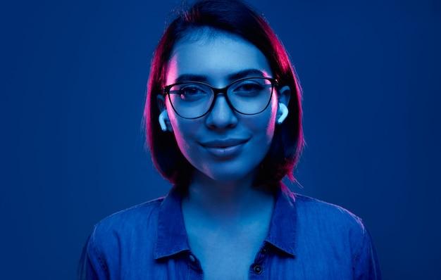 Młoda kobieta w okularach i słuchawkach w neonowym oświetleniu
