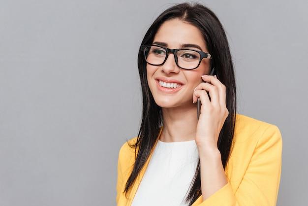 Młoda kobieta w okularach i ubrana w żółtą kurtkę, rozmawiając przez telefon na szarej powierzchni. spójrz na bok.