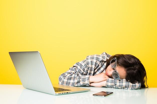 Młoda kobieta w okularach i wygląda na zmęczoną, śpi na biurku z laptopem, na białym tle