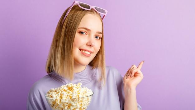 Młoda kobieta w okularach kinowych oglądając film 3d. uśmiechający się nastolatek dziewczyna widza filmowego w okularach z popcornem pokaż ręką na przestrzeni kopii na białym tle nad fioletowym kolorem ściany.