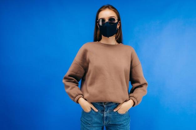 Młoda kobieta w okularach, maska medyczna i bluza z kapturem, pozowanie w studio na niebieskim tle
