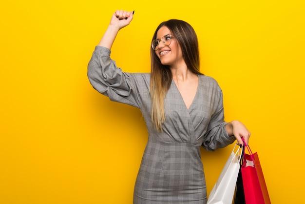 Młoda kobieta w okularach na żółtej ścianie, trzymając dużo torby na zakupy w pozycji zwycięstwa