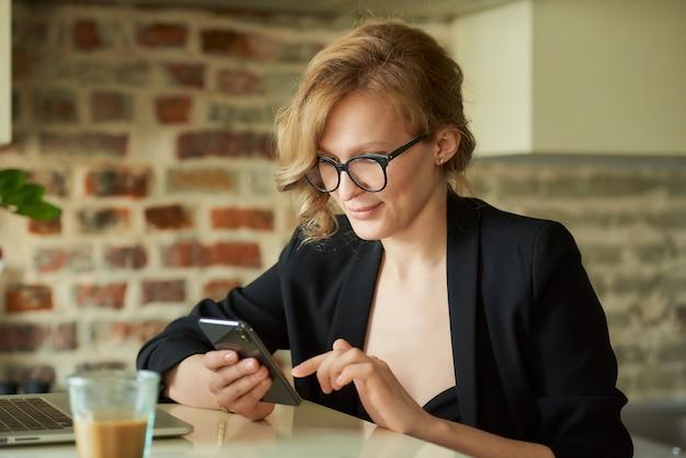 Młoda kobieta w okularach pracująca zdalnie w kawiarni. blond dama używa smartfona w domu. nauczycielka poszukująca informacji na temat telefonu komórkowego.