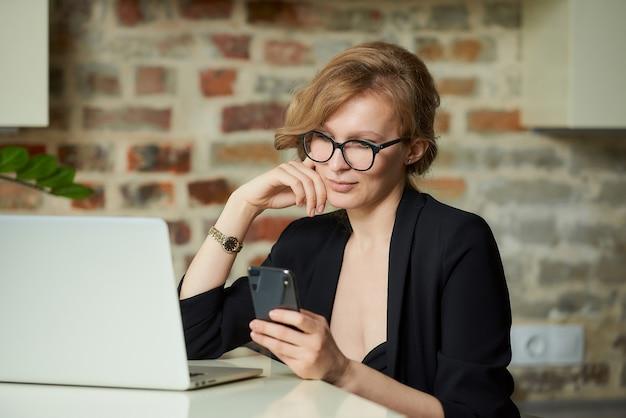 Młoda kobieta w okularach pracuje zdalnie na laptopie w kawiarni. blond dama używa smartfona w domu. nauczycielka poszukująca informacji na temat telefonu komórkowego.