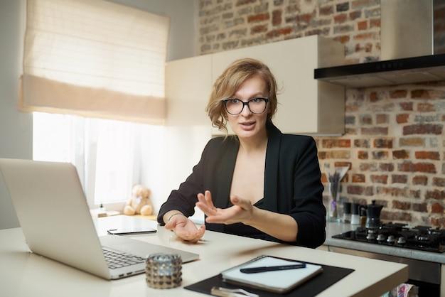 Młoda kobieta w okularach pracuje zdalnie na laptopie w swojej kuchni. blond dziewczyna gestykuluje, rozmawia z kolegami na wideokonferencji w domu.