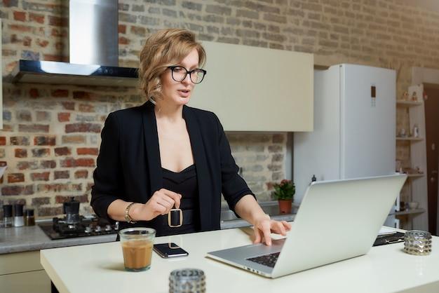 Młoda kobieta w okularach pracuje zdalnie na laptopie w swojej kuchni. poważna dziewczyna przeglądająca wiadomości w internecie w domu ..