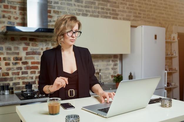 Młoda kobieta w okularach pracuje zdalnie na laptopie w swojej kuchni. poważna dziewczyna spokojnie przegląda wiadomości w internecie w domu.
