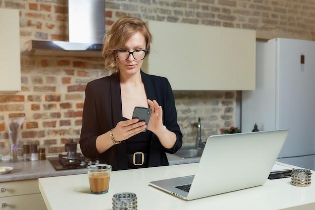 Młoda kobieta w okularach pracuje zdalnie w swojej kuchni. poważna dziewczyna spokojnie przegląda wiadomości w internecie ze swoim smartfonem w domu.