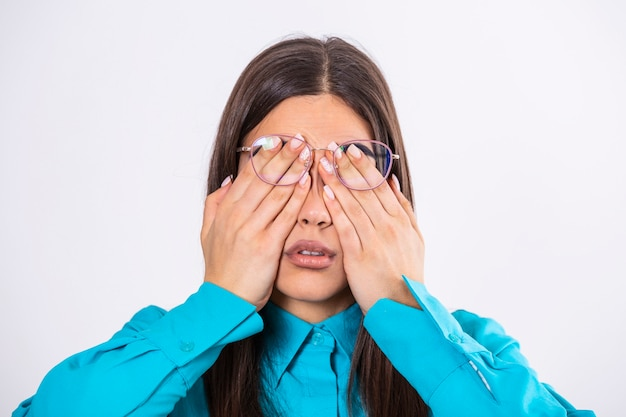Młoda kobieta w okularach przeciera oczy, cierpi na zmęczone oczy, koncepcja chorób oczu.