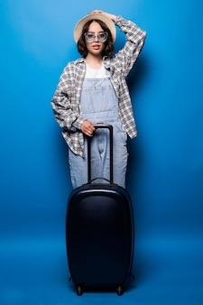 Młoda kobieta w okularach przeciwsłonecznych i kapeluszu z walizką, patrząc od hotelu na białym tle.