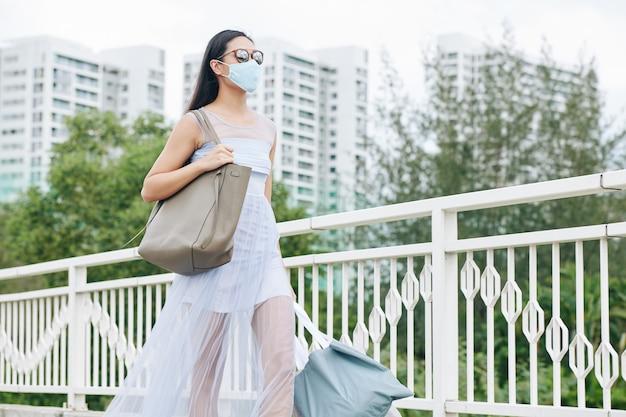 Młoda kobieta w okularach przeciwsłonecznych i letniej sukience na sobie maskę medyczną podczas spaceru po ulicy