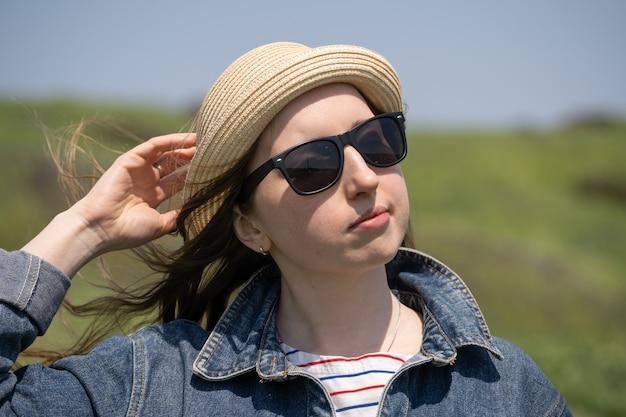 Młoda kobieta w okularach przeciwsłonecznych i słomianym kapeluszu na zbliżeniu natury. portret kobiety turystycznej na tle zielonych wzgórz. podróże.