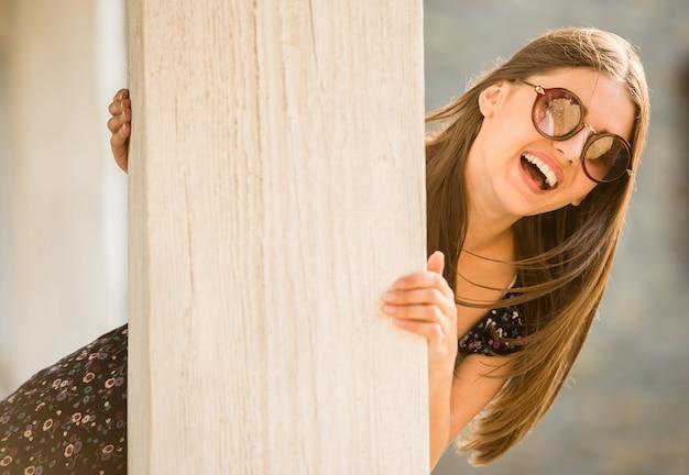 Młoda kobieta w okularach przeciwsłonecznych jest przyglądająca kamera.
