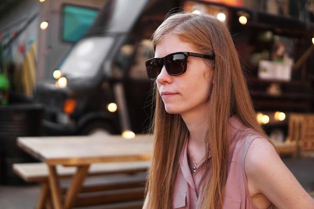 Młoda kobieta w okularach przeciwsłonecznych na tle czarnej ciężarówki z jedzeniem