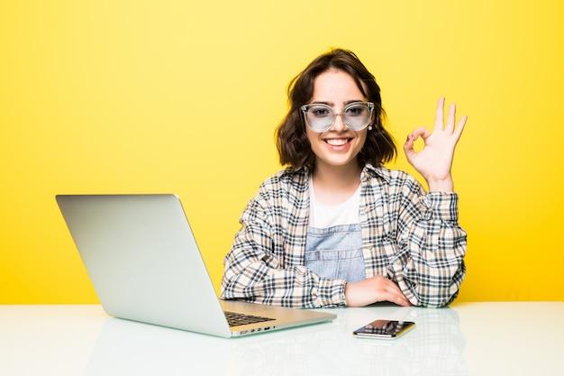 Młoda kobieta w okularach przeciwsłonecznych pokazuje znak ok na białym tle