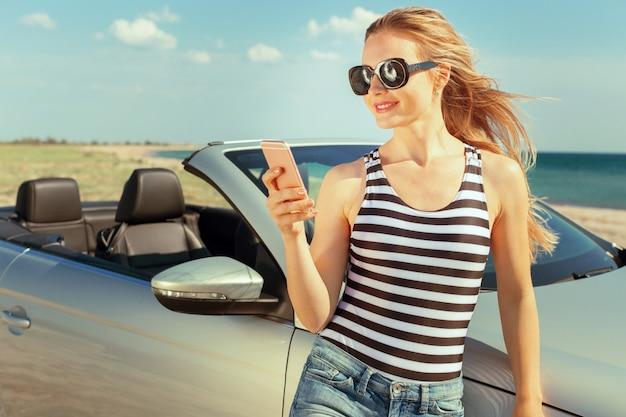 Młoda kobieta w okularach przeciwsłonecznych robi autoportretowi