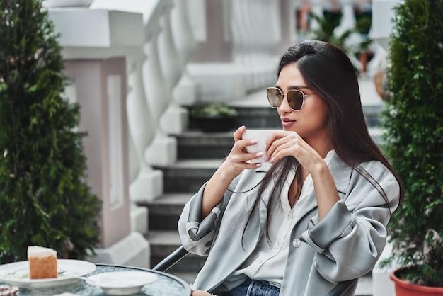 Młoda kobieta w okularach przeciwsłonecznych siedzi przy stole w kawiarni pije gorąco