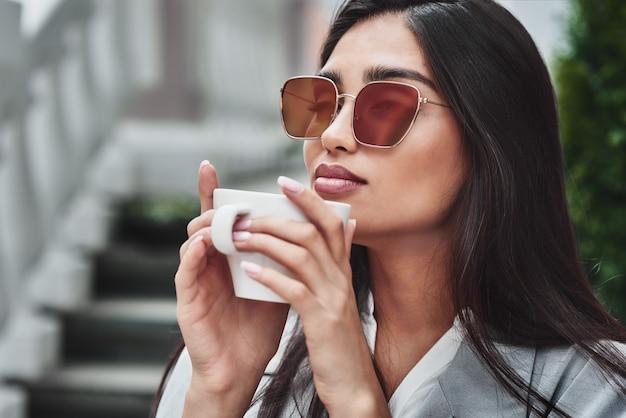 Młoda kobieta w okularach przeciwsłonecznych siedzi przy stole w kawiarni, trzymając kubek s