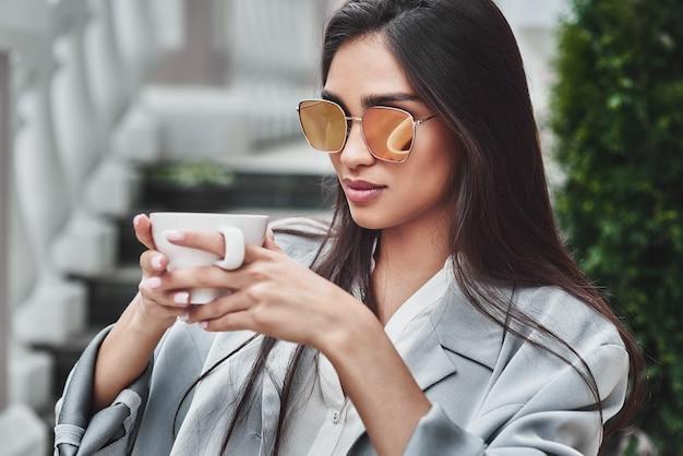 Młoda kobieta w okularach przeciwsłonecznych siedzi przy stole w kawiarni z filiżanką c