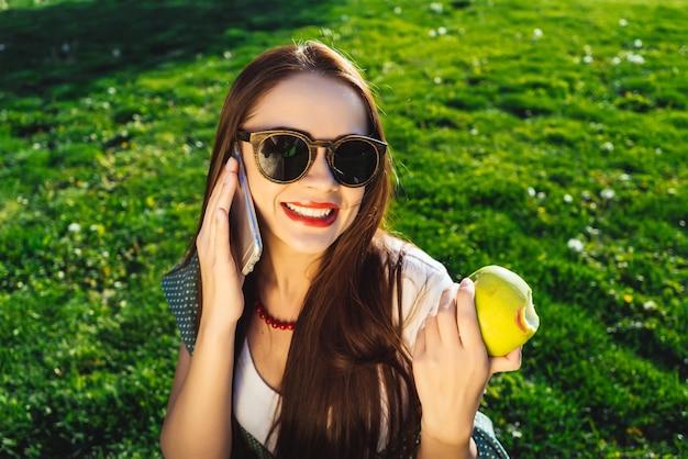 Młoda kobieta w okularach przeciwsłonecznych siedzi w parku, na trawniku z jasnozieloną trawą, uśmiecha się, je jabłko, rozmawia przez telefon