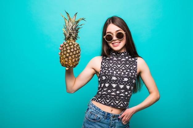 Młoda kobieta w okularach przeciwsłonecznych ubranie z ananasem w rękach na białym tle
