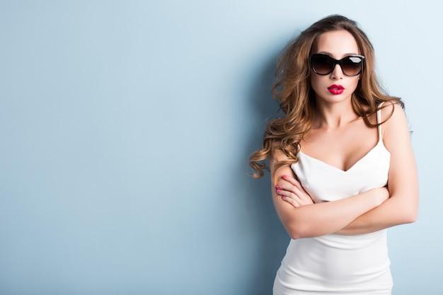 Młoda kobieta w okularach przeciwsłonecznych w studiu.