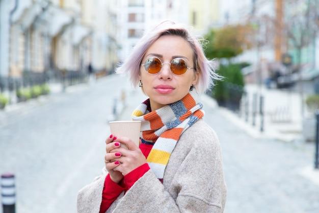 Młoda kobieta w okularach przeciwsłonecznych z filiżanką kawy