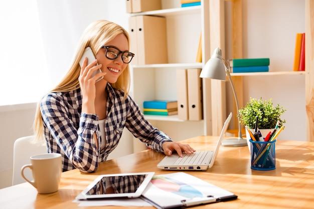 Młoda kobieta w okularach rozmawia przez telefon i pracuje z laptopem