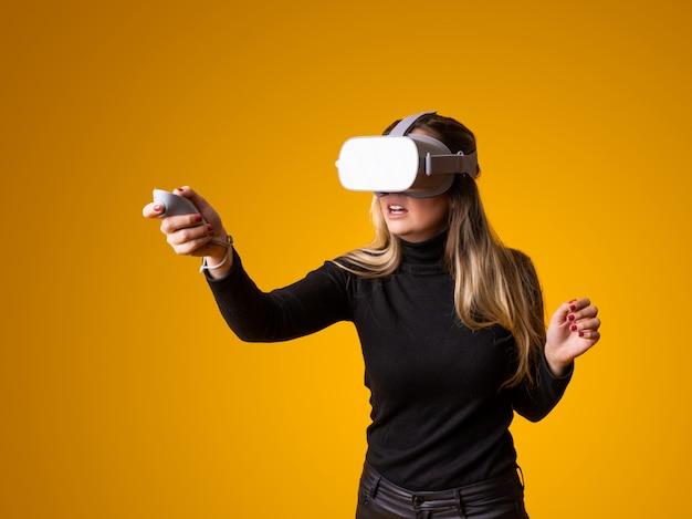 Młoda kobieta w okularach rzeczywistości wirtualnej uśmiechnięty i skoncentrowany, grając w gry wideo