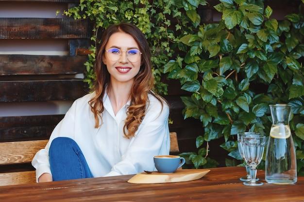 Młoda kobieta w okularach siedzi przy stoliku w kawiarni