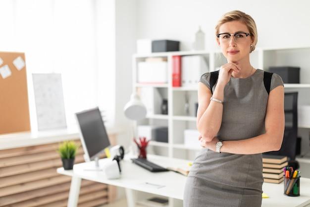 Młoda kobieta w okularach stoi przy stole w biurze.