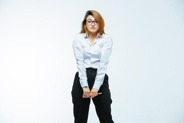 Młoda kobieta w okularach trzyma długopis i wygląda na zdziwioną