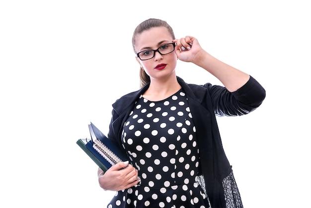 Młoda kobieta w okularach trzymając książki na białym tle na białej ścianie
